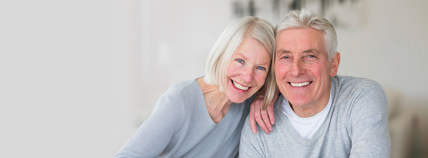 Elderly couple leaning on each other smiling
