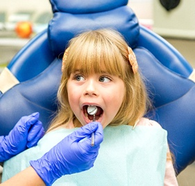 blonde headed girl receiving dental exam