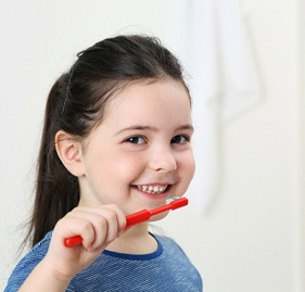 young girl brunette brushing her teeth