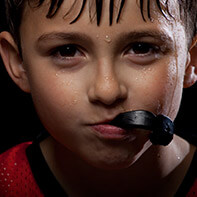 Boy mischievously biting on mouthguard