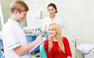 Lady conversing with dentist and assistant