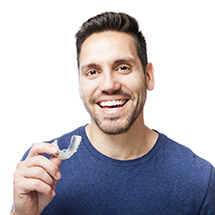 Man holding clear aligner smiling