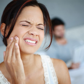 Lady in excruciating pain holding cheek